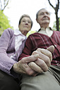Germany, Cologne, Senior couple holding hands in park - JAT000056