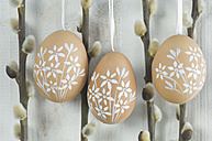 Painted easter eggs hanging on wooden wall - ASF004969
