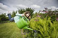 Germany, Bavaria, Kaufbeuren, Mid adult woman watering plants in garden - CAF000014