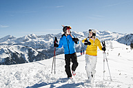 Austria, Salzburg, Young man and woman walking in snow with skies, smiling - HH004611