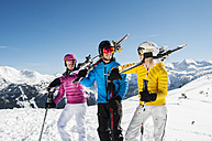 Austria, Salzburg, Young man and young women standing in snow with skis - HH004613