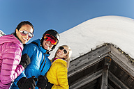 Austria, Salzburg, Young man and young women standing in front of alpine hut - HH004631