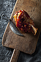 knuckle of pork with knife on chopping board, close up - CSF019325