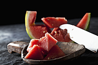 Slices of watermelon with knife on wooden spoon, close up - CSF019334