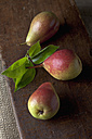 Pears with leaves on chopping board, close up - CSF019374