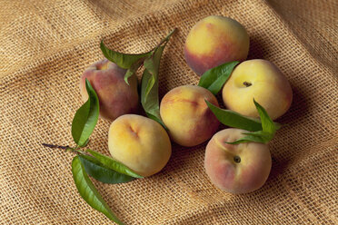 Peaches on leaves on sack, close up - CSF019363