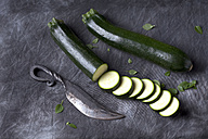 Courgette with knife on black textile, close up - CSF019358
