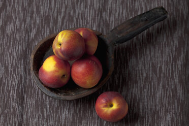 Peaches on wooden spoon, close up - CSF019355