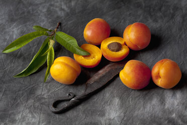 Apricots with leaves and knife on black textile, close up - CSF019353