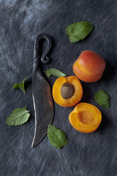 Apricots with leaves and knife on black textile, close up - CSF019350