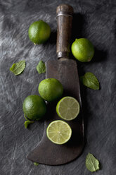 Limes with leaves and sickle on black textile, close up - CSF019347