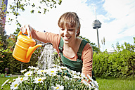 Germany, Cologne, Young woman watering flowers, smiling - RHYF000407