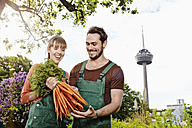 Germany, Cologne, Young couple holding bunch of carrots, smiling - RHYF000408