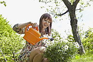 Germany, Cologne, Young woman watering flowers, smiling - RHYF000425