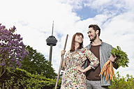 Germany, Cologne, Young couple holding bunch of carrots, smiling - RHYF000438