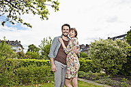 Germany, Cologne, Young couple embracing each other in garden, smiling - RHYF000415