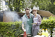 Germany, Cologne, Young couple barbecueing, smiling - RHYF000383