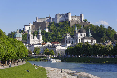 Austria, Salzburg, View of Collegiate Church and Hohensalzburg Castle at River Salzach - SIE003935