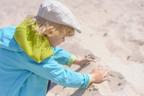 Germany, Mecklenburg Western Pomerania, Boy playing with sand at baltic sea - MJF000185