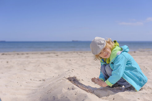 Germany, Mecklenburg Western Pomerania, Boy playing with sand at baltic sea - MJF000186