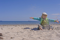 Germany, Mecklenburg Western Pomerania, Boy playing with sand at baltic sea - MJF000189