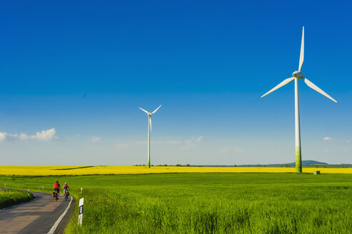 Germany, Saxony, Wind turbines in oilseed rape field - MJF000180