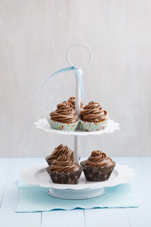 Cupcakes topped with chocolate buttercream on cake stand, close up - ECF000179