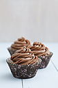 Cupcakes topped with chocolate buttercream on wooden table, close up - ECF000176