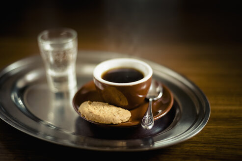 Espresso black coffee with cookie and glass of water on tray - MJ000193