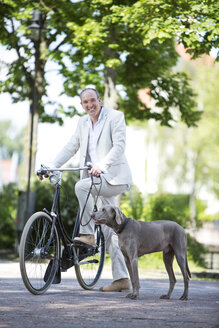 Germany, Bavaria, Portrait of mature man with Weimaraner dog and bicycle, smiling - MAEF006826