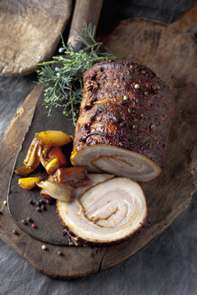 Rolled roast pork and braised vegetables on wooden board, close up - CSF019435