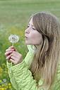 German, Bavaria, Starnberg, Girl blowing dandelion seed - CR002428