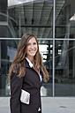 Germany, Berlin, Portrait of businesswoman holding newspaper, smiling - FKIF000001