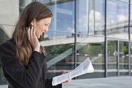 Germany, Berlin, Businesswoman reading newspaper, smiling - FKIF000002