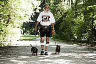 Germany, Bavaria, Munich, Senior man walking with dogs in english garden - ED000027