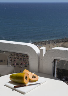 Spain, Gran Canaria, Papaya with knife on table near beach - MAB000099