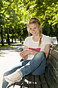 Germany, Berlin, Portrait of young woman sitting on bench with mobile phone, smiling - BFR000226