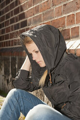 Germany, Berlin, Depressed young woman sitting against wall - BFR000229