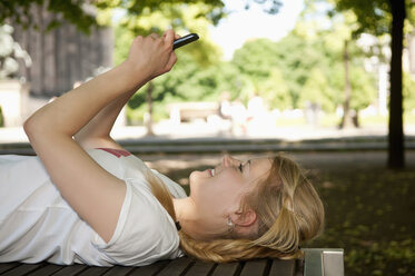 Germany, Berlin, Young woman lying on bench and using mobile phone, smiling - BFR000234