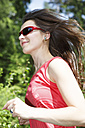 Germany, Mid adult woman jogging in forest, smiling - VT000006