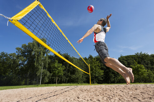 Germany, Mature man playing beach volleyball - STSF000030