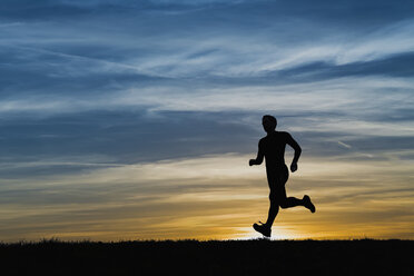 Germany, Mature man jogging at sunset - STSF000014