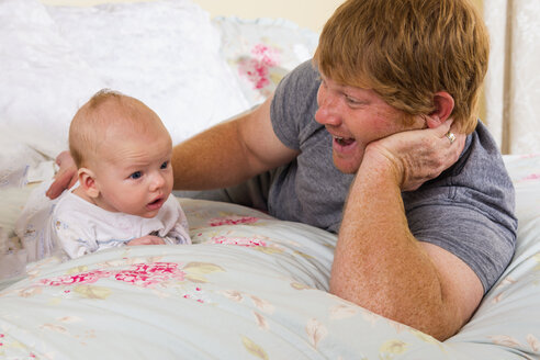 Father and son lying on bed, smiling - ABAF000882