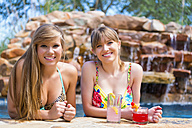 Portrait of young women sitting at swimming pool, smiling - ABAF000886