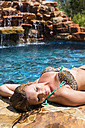 Young woman sunbathing at poolside - ABAF000898