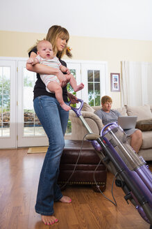 Mother with son using vacuum cleaner while father in background - ABAF000944