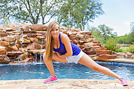 Young woman doing yoga at swimming pool, smiling - ABAF000888