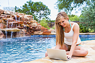 Young woman using laptop at swimming pool, smiling - ABAF000881