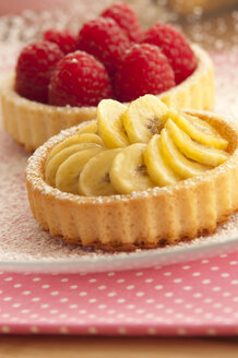 Banana and raspberry tartlets on plate, close up - OD000040
