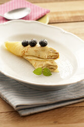 Crepe with custard and blueberries on plate, close up - OD000048